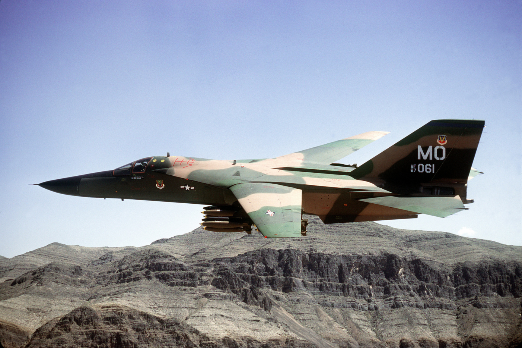 left_side_view_of_an_f-111a_aircraft_banking_to_the_left_near_nellis_air_force_basek.png