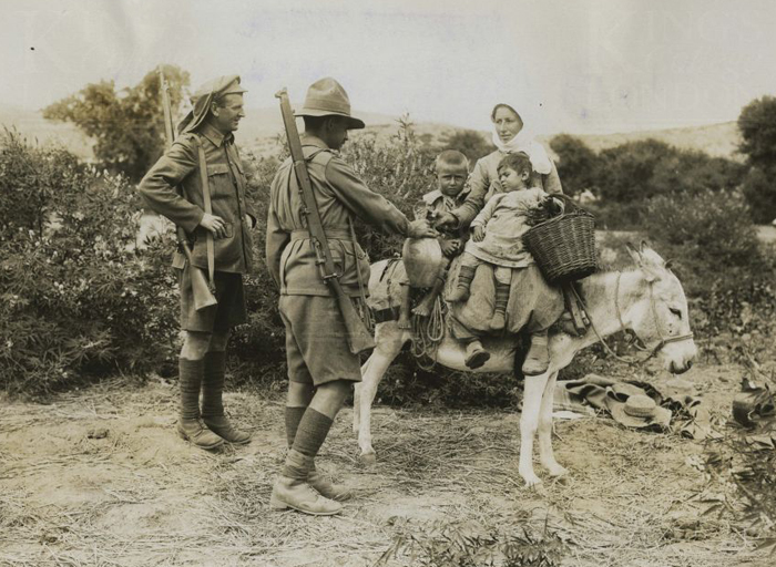 anzac_soldier_and_british_soldier_with_turkish_woman_her_children_and_donkey.jpg