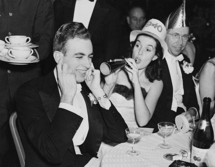 Egy hölgy trombitát fúj barátja fülébe 1940-ben egy újévi ünnepségen.