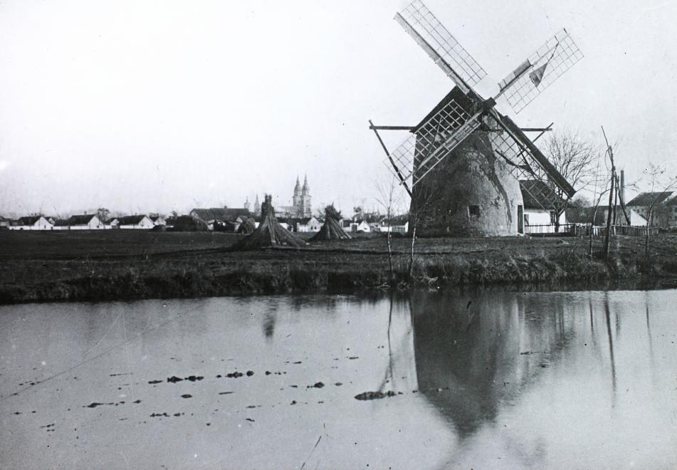1902_kiskunfelegyhaza_szelmalom_a_tavolban_a_szent_istvan_kiraly_templom_magyar_foldrajzi_muzeum_diagyujtemeny.jpg