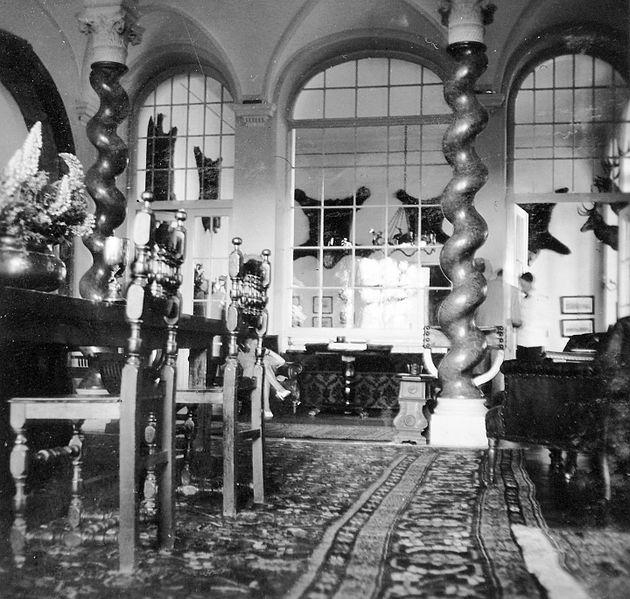 1940. A kastély csavart oszlopos szalonja, hátul a Hubertus terem medvebőrökkel. Kép: Fortepan / Gyöngyi