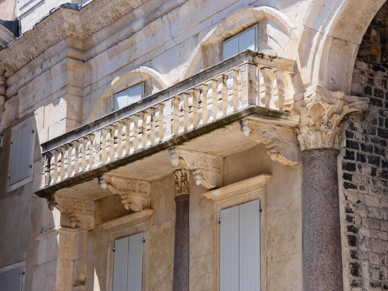 A Peristiliumhoz később hozzáépített erkély. Az erkélyt tartó konzolokon szereplő virágminták visszaköszönnek a korláton.