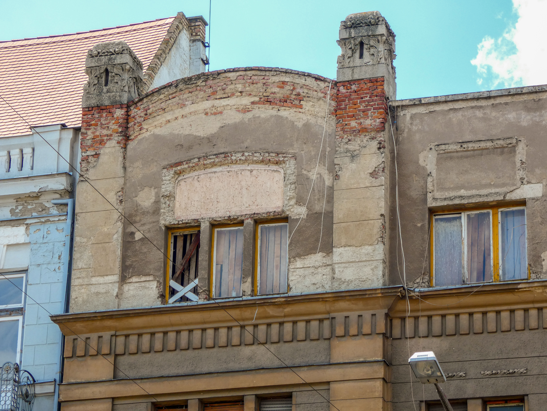 A vakolat néhol rendesen lekopott. A legfelső szint ablakai felett hiányzó elemek, talán díszítés helye látszik.
