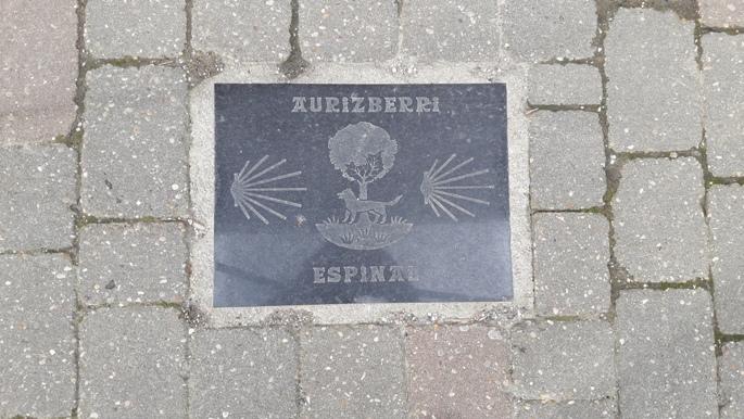 El camino Aurizberri, jelzőkő az utcaburkolaton.