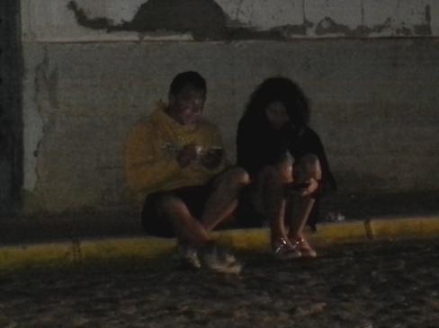 Márti és Giuseppe erősen koncentrálva wifiznek a ház előtt a járdán ülve...