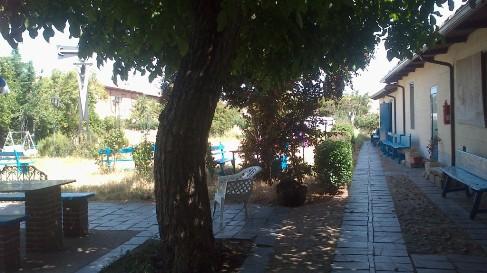A big garden. A kis átjárón keresztül egy hatalmas hátsó kertbe jutunk, ahol mindenféle kényelmes kerti eszköz szolgálja a zarándokok nyugalmát. És még szobák is vannak! :-)