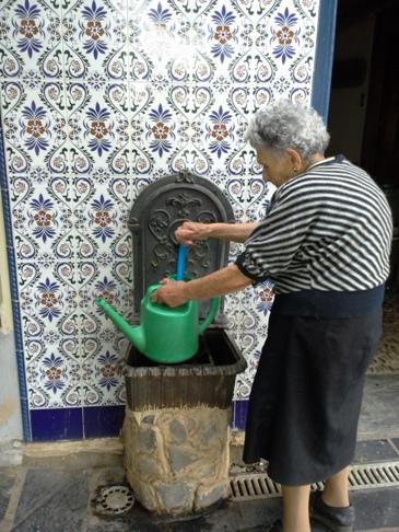 Senora Joaquina, éppen vizet vesz a falikútból a virágok locsolásához.