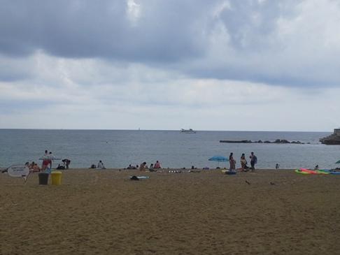 Barcelona beach, homokos tengerpart néhány fürdőzővel.
