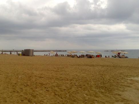 Homokos tengerpart felhőkkel és napernyőkkel.