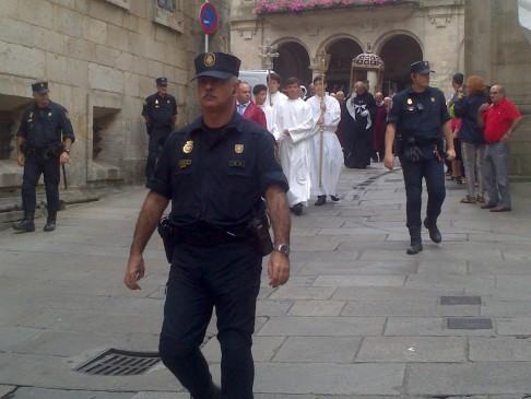 A biztonságiak gyűrűjében vonulnak az egyházi méltóságok.