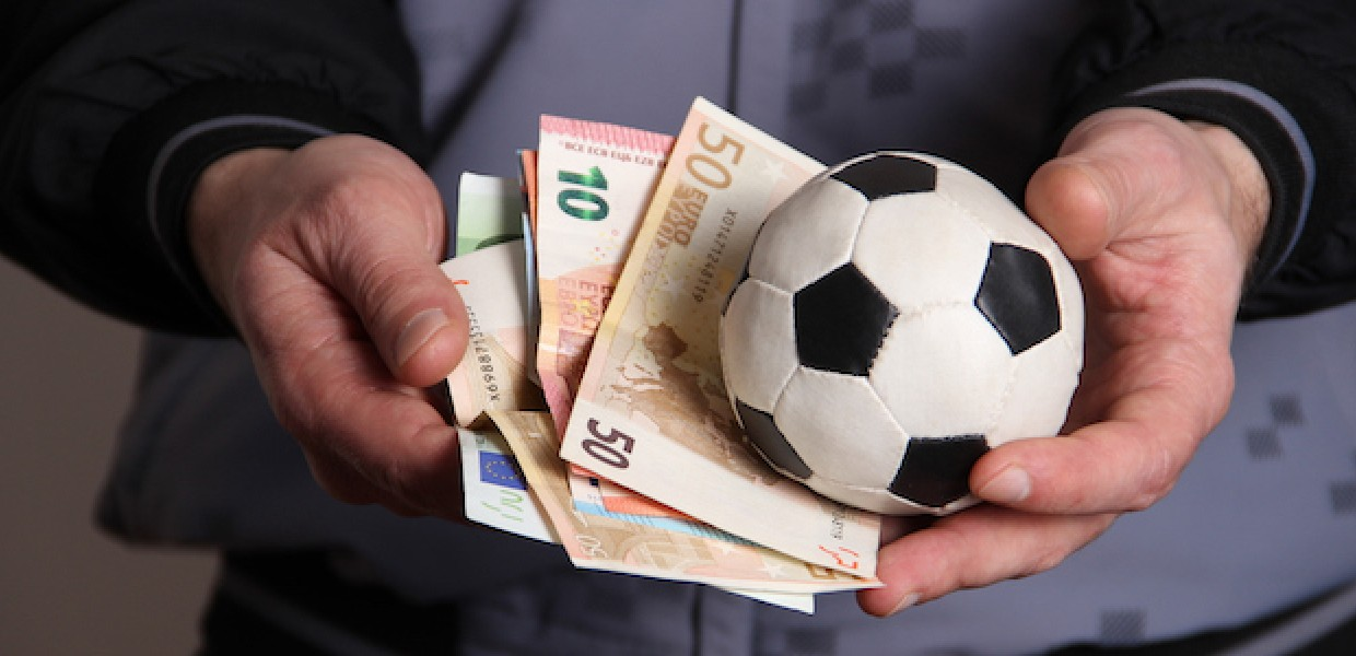 man_holding_football_and_money_in_his_hands_dc29a70b0b42d6163499b3da6f075354.jpg