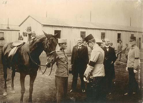 A trónörököspár a Pozsonyi úti rokkant katonák iskolájában és műhelyében, 1915 augusztusában. Károly főherceg Puju János szakaszvezetővel beszélget. Mögöttük Berecz Gyula királyi tanácsos, jobbra, egyenruhában dr. Dollinger Gyula áll