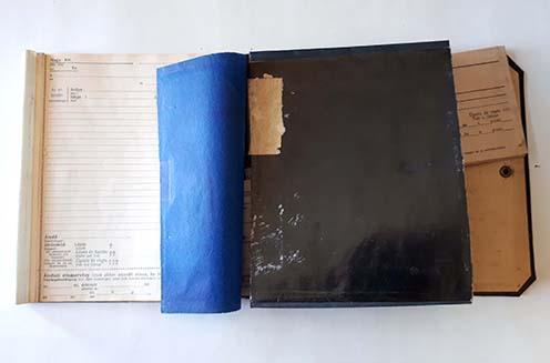 Honvéd ezredbeli tiszt perforált jelentőtömbje, a lapok alól félig előhúzott indigók egyikével és a tokból félig kihúzott, előre nyomtatott boríték, amelybe a megírt jelentést kellett betenni. A külső kemény fekete kartonlap patent segítségével záródott, ennek egyik fele látható jobb oldalon