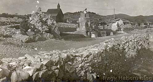 """A tábor északnyugati bejárata a József főherceg út elején álló, ma is meglévő emlékművel és a sziklába faragott úgynevezett """"Boroević székével"""". A háttérben az ortodox kápolna"""