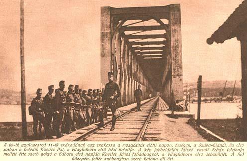 """Az eredeti képaláírás: """"A 68-ik gyalogezred 11-ik századának egy szakasza a mozgósítás előtti napon, őrségen a Száva-hídnál. Az első sorban a hetedik Kovács Pál, a világháború első hősi halottja. A kép jobboldalán látszó vasuti őrház telefonja mellett érte szerb golyó a háború első napján Knerler János főhadnagyot, a világháború első sebesültjét. A híd közepén, fehér zubbonyban szerb katona áll őrt."""""""