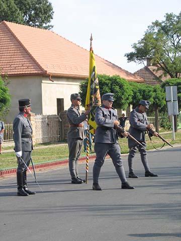 Háromszoros díszsortűz, a háttérben a cs. és kir. szolnoki 68. gyalogezred egykori hadilobogója