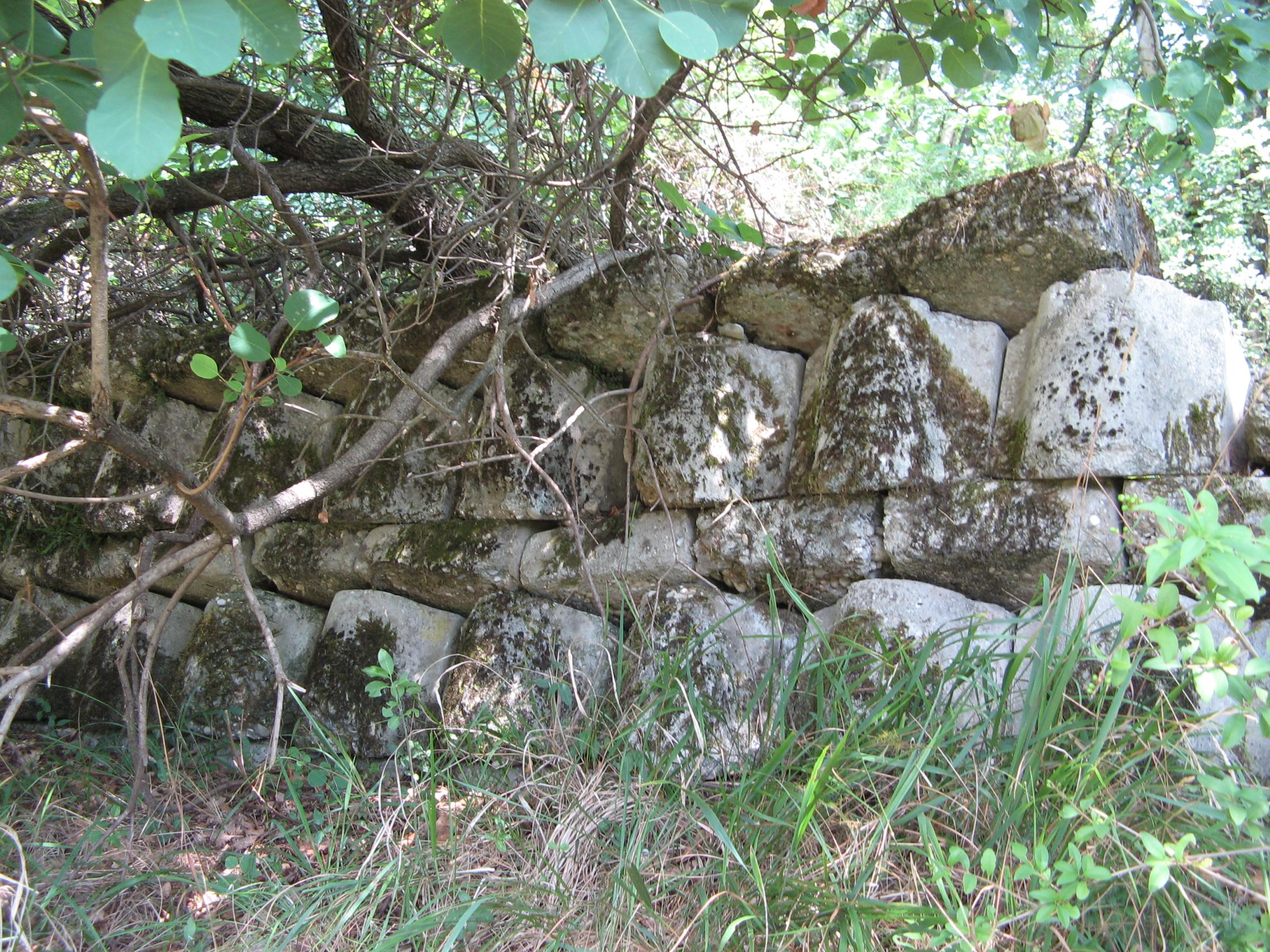 Muro di pietra costruito con pietre tombali sul lato settentrionale del cimitero militare accanto al cimitero comunale di una volta