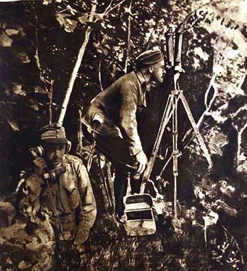 """""""Tüzérségi megfigyelőhely az erdő szélén. A bokrok között periszkóp segítségével figyeli az egyik tüzértiszt a közelben elhelyezett üteg lövegeinek hatását, s tapasztalatait közli azután a közelében levő tüzérrel, aki tábori telefonon tovább adja a híreket az üteg parancsnokának."""""""