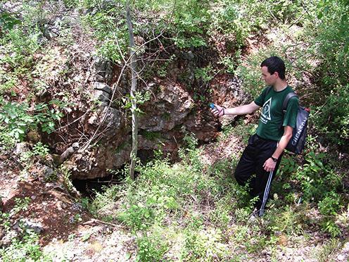 """Az aknafúrás kiindulópontjául is szolgáló kaverna bejárata a terület 2006-ban történt bejárása és felmérése során. A képen Blaskó Dénes térképész hallgató barátunk rögzíti a """"minengang"""" bejáratának GPS koordinátáit"""