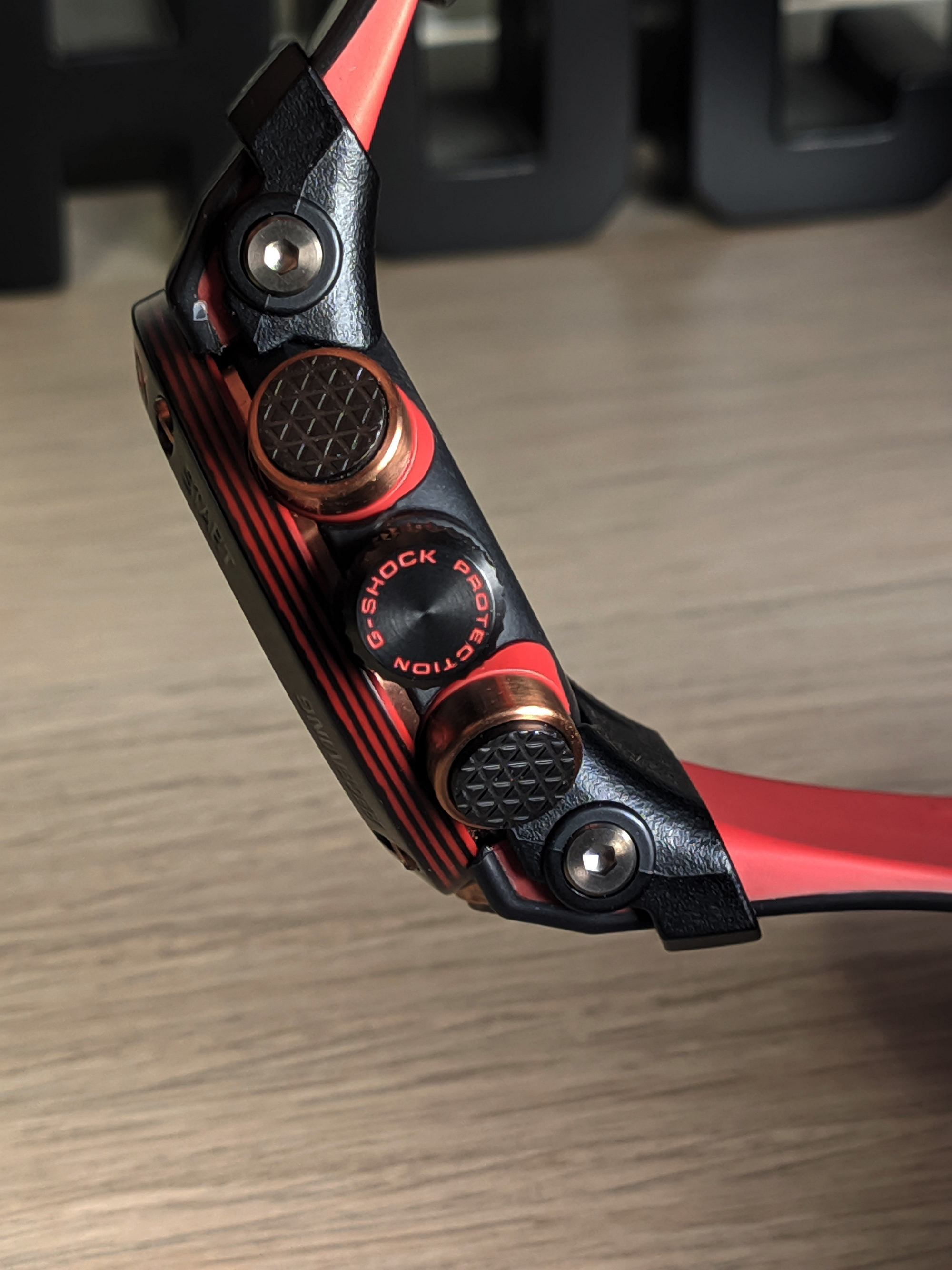 Gomb, csavar van bőven, ez egy G-Shock. Jól látszik a rétegezett szénszálas anyag, itt vörös-fekete.
