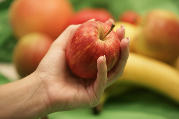 Food-hand-holding-apple-other-fruit-in-background.jpg