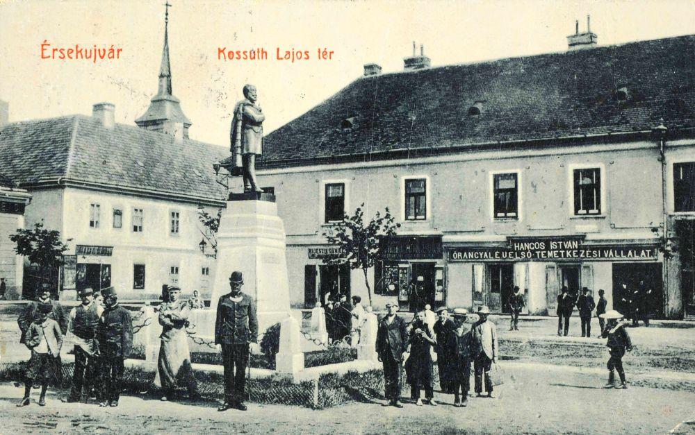 Érsekújvár, Kossuth Lajos tér (a szobor háta mögött a Ferencrendi zárda látható, emeleti ablakai között a Bercsényi-emléktáblával) – Térkép-, Plakát-, és Kisnyomtatványtár. Jelzet: E 754.