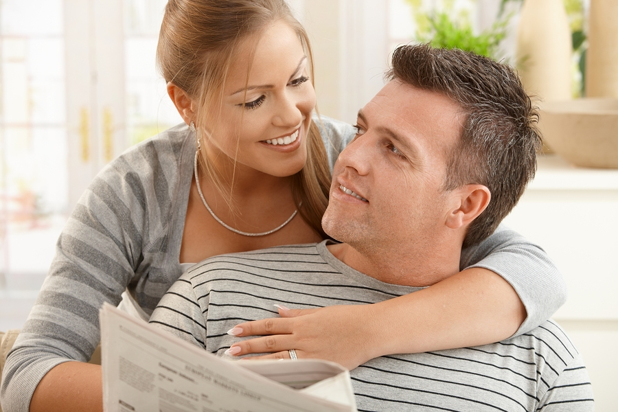 bigstock-happy-couple-sitting-at-home-l-13100603.jpg