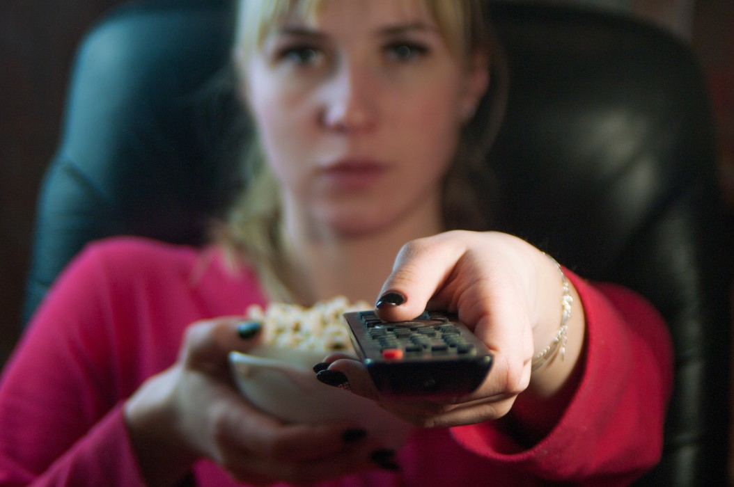 girl-eating-popcorn-and-watching-tv-switching-channels-by-pressing-buttons-on-the-remote-woman_t20_29vkko.jpg