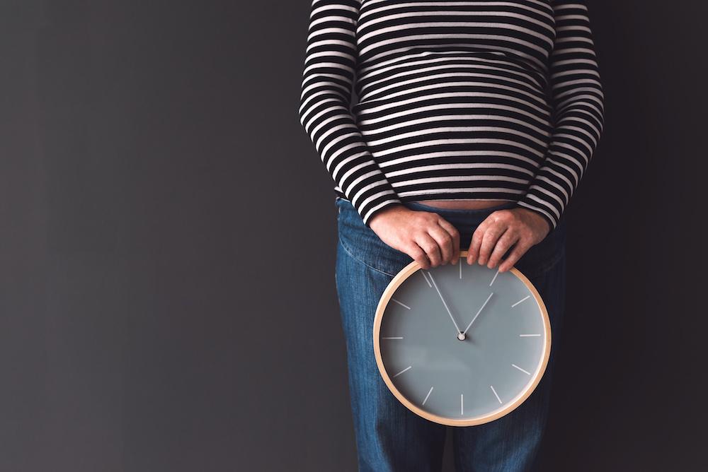 pregnant-female-with-vintage-alarm-clock-p8nbp7z.jpg