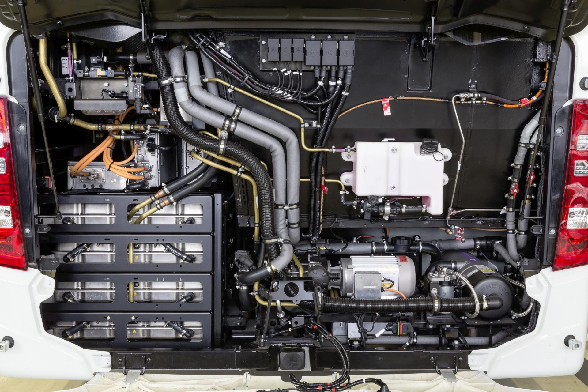 A motortér. A jobb oldalon jól látszik az elektromos légsűrítő szürke villanymotorja és mellette jobbra a kisegítő fűtés. A belőle kiinduló és a tető felé tartó fekete cső a füstgáz elvezetés, tehát részben gázolajos. (Kép: Daimler)