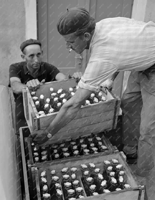 Sellye, 1961. július 17. A földműves-szövetkezet dolgozói járműre pakolnak több ládányi saját gyártású üdítőitalt a kiszállításhoz. A szövetkezetben a négyféle ízben előállított itallal naponta 1000-1200 csatos üveget töltenek meg, s jövőre ezt a mennyiséget még tovább növelik. MTI Fotó: Kovács Lajos