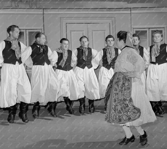Vajszló, 1960. február 1. Spang Árpádné, a helyi Földműves-szövetkezet (FMSZ) hitelszövetkezetének dolgozója az Ormánsági lakodalmas című előadást próbálja a vajszlói művészegyüttes tagjaival. Az együttes a darabot felszabadulásunk 15. évfordulója alkalmából meghirdetett ifjúsági seregszemlén mutatja be először. MTI Fotó: Bereth Ferenc