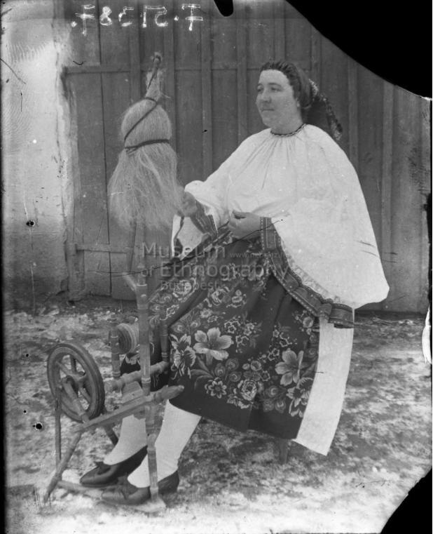 Fonó asszony biklában, főkötőben a rokka mellett<br />Vajszló, 1910-es évek<br />ff., üvegnegatív, 9x12 cm
