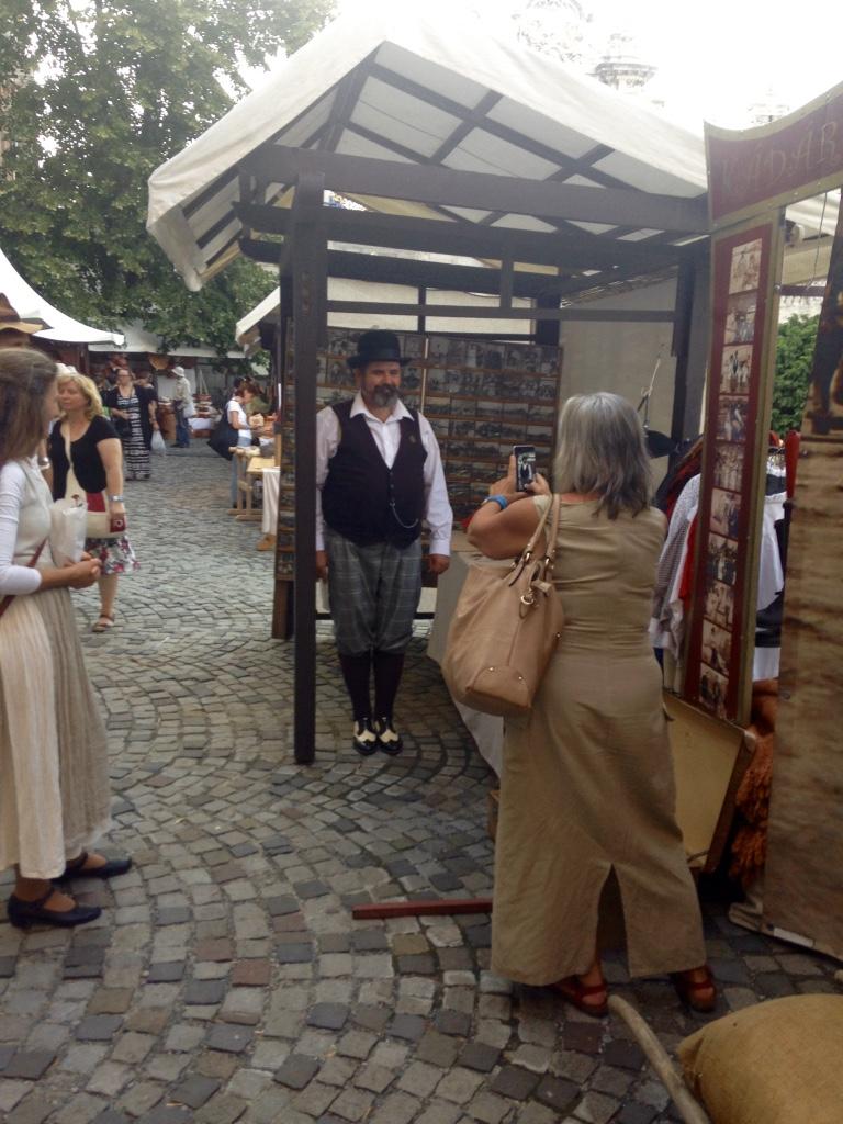 A vásári fotóst fotózzák. Az úriember idén két csodás háttérrel, az esküvőssel és a piacozóssal érkezett