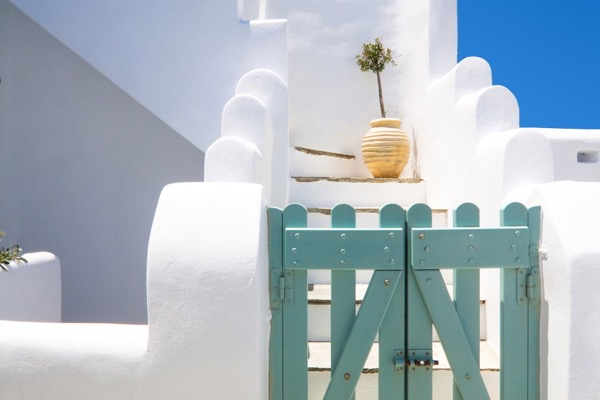 traditional-greek-house-against-blue-sky-with-a-small-olive-tree.jpg