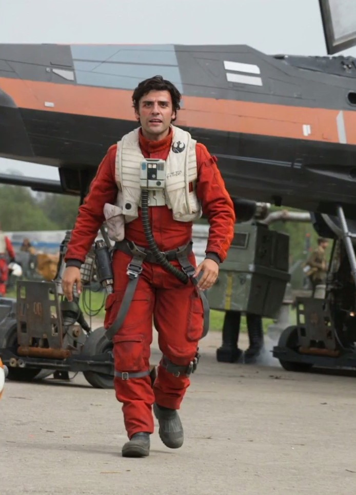 Oscar Isaac a pilóta öltözetben. A háttérben egy klasszikus 'energia droid'.
