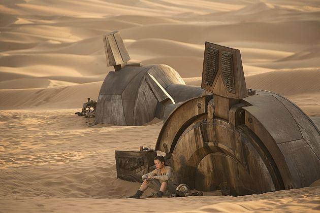 Rey (Daisy Ridley) hűsöl egy kidőlt lépegető lábának tövében.