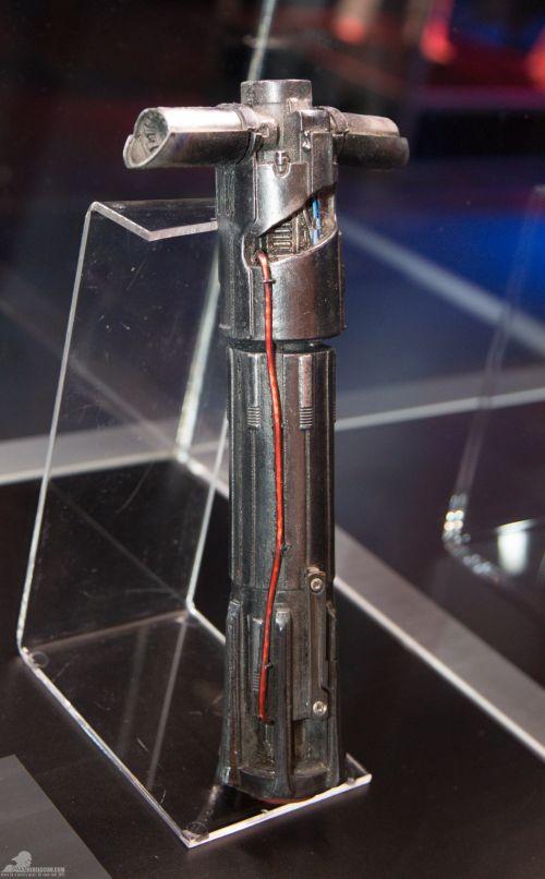 Kylo Ren fénykardjának markolata 3D nyomtatással készült. Érdemes megfigyelni a 'sufnituning' jelleget, a megbontott burkolattal. A kedvencem az u-szöggel odafogott drót. :)<br /><br />(fotó: rebelscum.com)