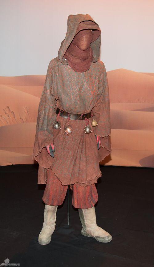 Sivatagi nomád a Jakku bolygóról.<br /><br />A köpeny és nadrág pamutból készült. Az öv anyaga bőr és fém. A kesztyű pamut és gumi, a csizma pamutot és bőrt is tartalmaz.<br /><br />(fotó: rebelscum.com)