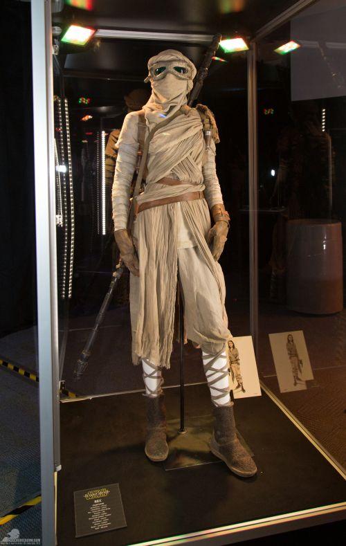 Rey a sivatag lakója. Az ő jelmeze az egyik legkidolgozottabb.<br /><br />Néhány anyag, amit a tervezők használtak: A törzset viszkóz szövetbe burkolták. A fejet és a kart pamut fásli borítja. Az öltözet felső része kenderből és pamutból készült. A nadrág selyem. A csuklópánt, az öv és a kesztyű bőrből van. A csizma anyaga bőr és gyapjú.<br /><br />(fotó: rebelscum.com)