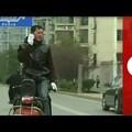 Őrült kínai háttal, állva és telefonálva motorozik