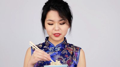 stock-footage-pretty-young-chinese-woman-eating-noodles-from-a-bowl-with-chopsticks.jpg
