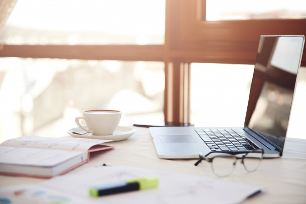 lateral-foreground-working-desk-with-laptop-cup-coffee-eyeglasses-stationery_8353-10541.jpg