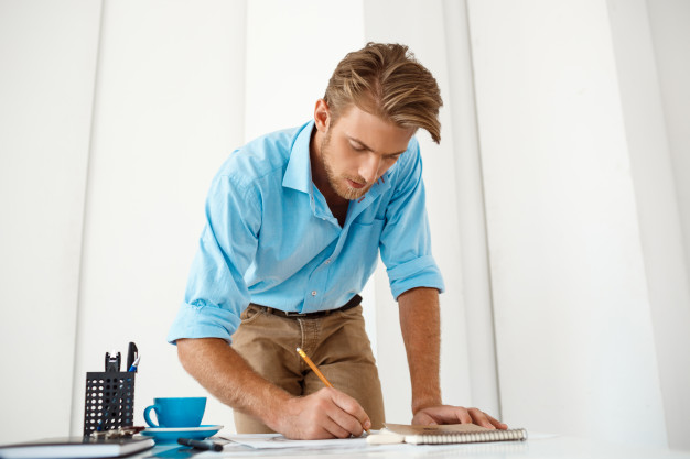 young-handsome-confident-pensive-businessman-working-standing-table-writing-notepad-white-modern-office-interior_176420-2612.jpg