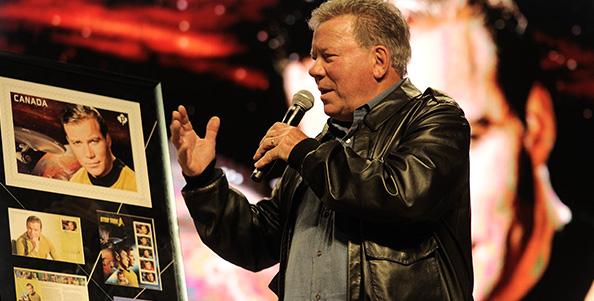 A Captain Kirk alakításáért legendássá vált színész, William Shatner méltatja a róla mintázott bélyeget a Calgary Comic and Entertainment Expo-n, áprilisban. Forrás: www.canadapost.ca