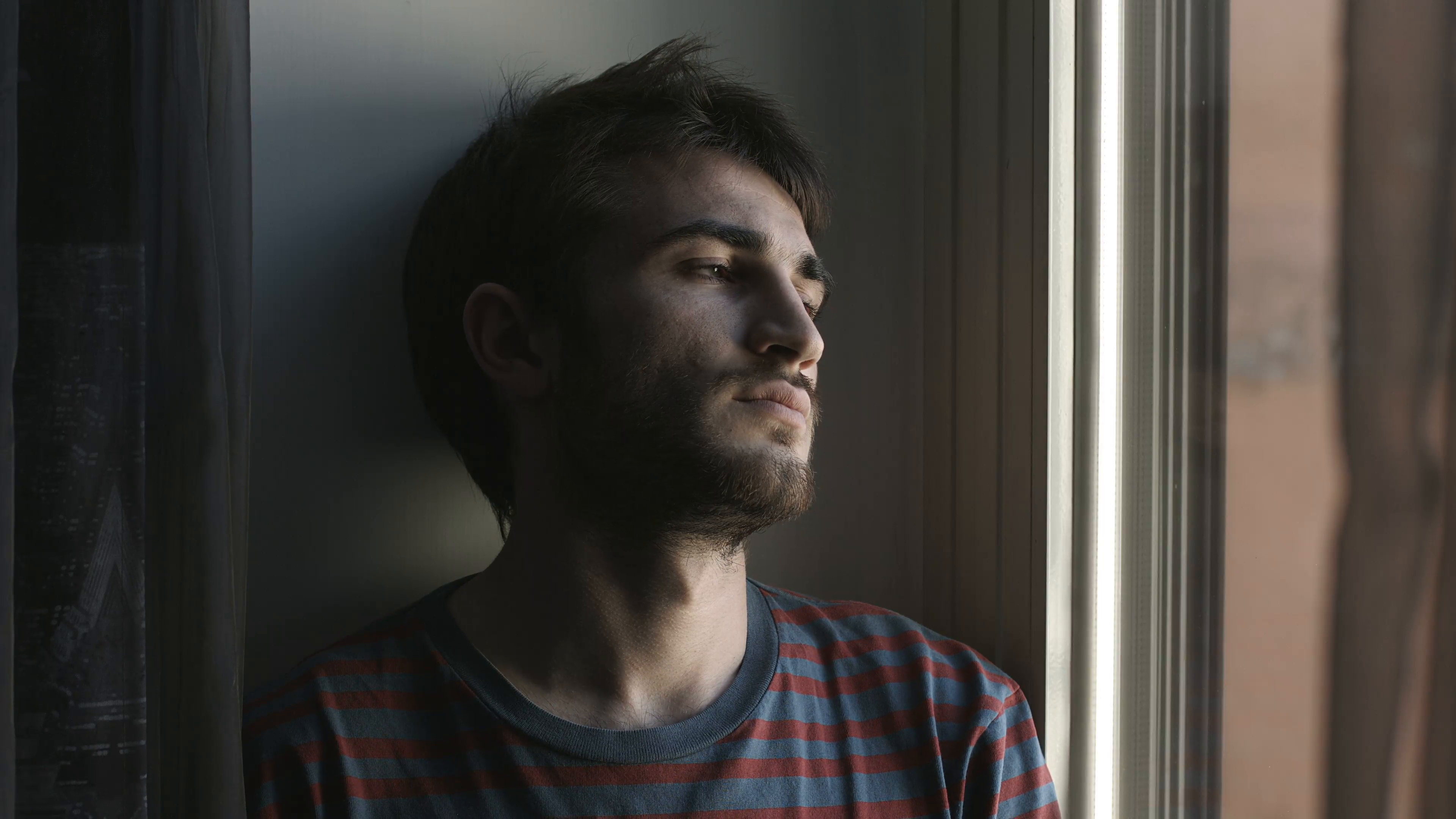 portrait-of-handsome-young-sad-man-in-front-of-a-window-4k_emzzbinke_f0000.png