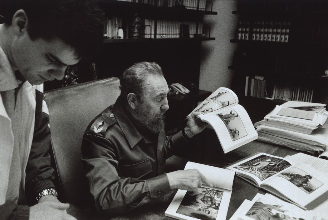 Fidel Castro éppen a kubai forradalomról készült képeket nézi.