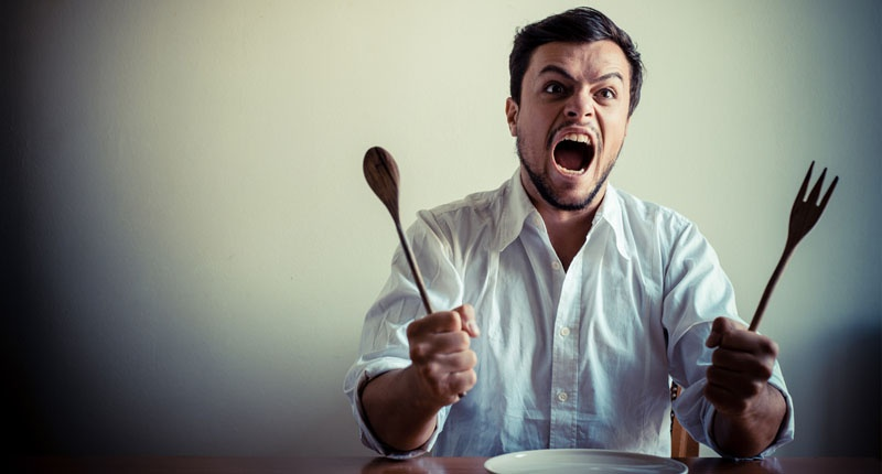 angry-man-waiting-for-food-with-a-large-wooden-spoon-and-fork-shutterstock-800x430.jpg