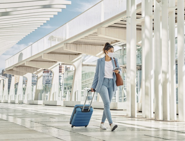 woman-with-luggage-during-pandemic-airport_23-2148789910.jpg