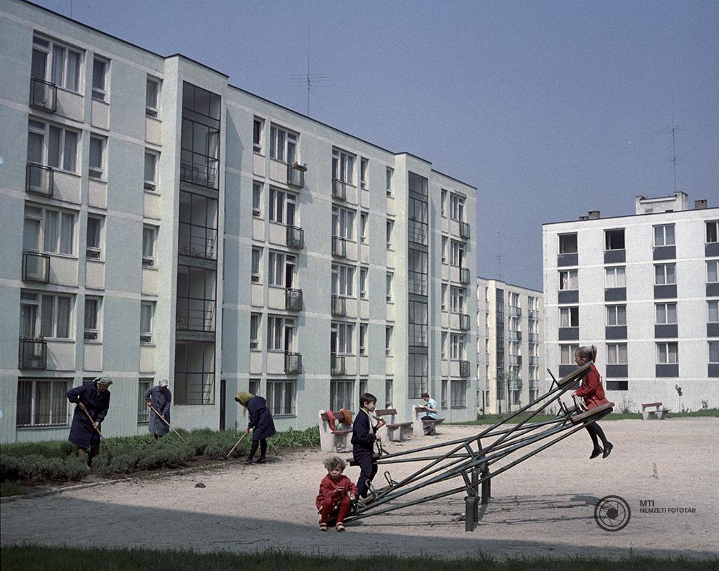Tatabánya, 1966. április 27. Gyerekek mérleghintáznak a játszótéren, miközben kertészek parkosítanak az új városrész lakóházai között. MTI Fotó: Hadas János